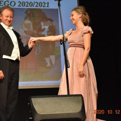 Wokalista trzyma dłoń kobiety ubranej w różową suknie na scenie