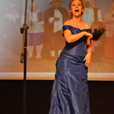 Pani w niebieskiej sukni śpiewają na scenie