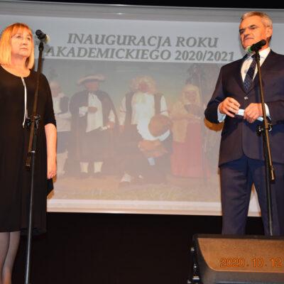 Dwoje osób stojących na scenie przed mikrofonem