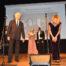 Cztery osoby elegancko ubrane, występują na scenie